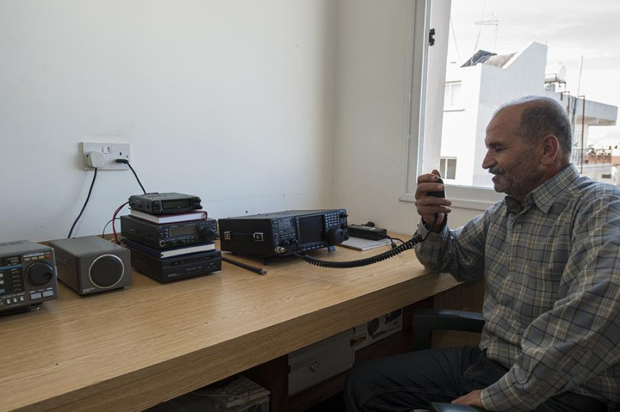 Ismail, 1B1AH, in his tidy radio room. The G5RV dipole is visible outside the window.