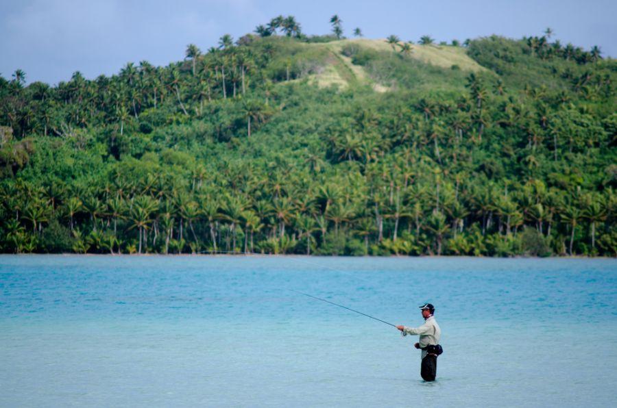 Остров Аитутаки E51WET Туристические достопримечательности Рыбак рыбачит с целью выловить рыбу альбула bonefish.