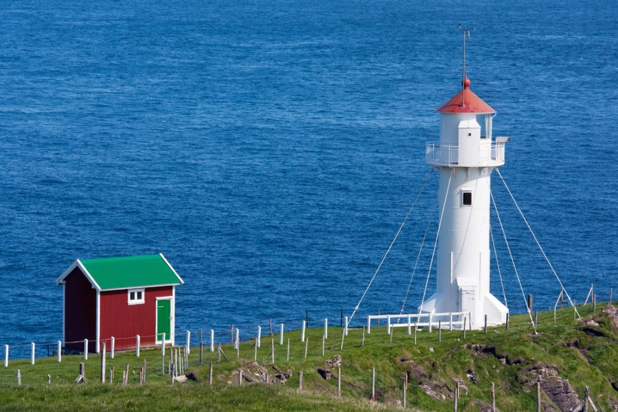 Faroe Islands S79SP DX News White lighthouse and red cabin on a sea cliff Akraberg, Suduroy, Faroe Islands