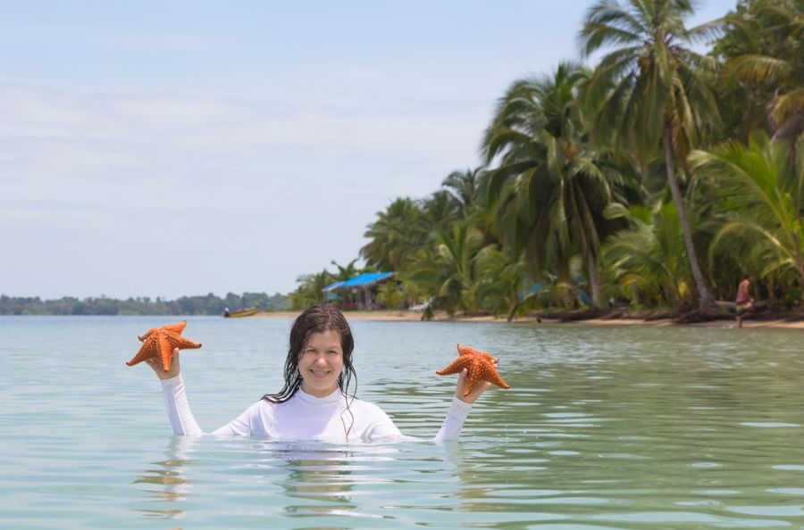 Panama HO2C Tourist attractions spot Woman with two starfish in hands, archipelago Bocas del Toro.
