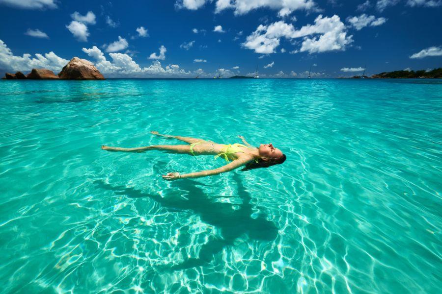 Сейшельские острова S79CD Туристические достопримечательности Девушка в желтом бикини лежит на воде.