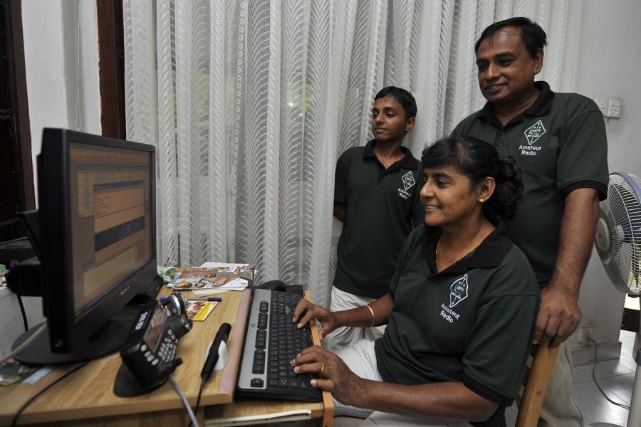Sri Lanka Sitting: Rajini, 4S6ARW, makes a digital QSO on the 10-meter band, while Senarath, 4S6WAS, stands behind her. Their son, Reshan, 4S6YRW, is supervising his mother in action.
