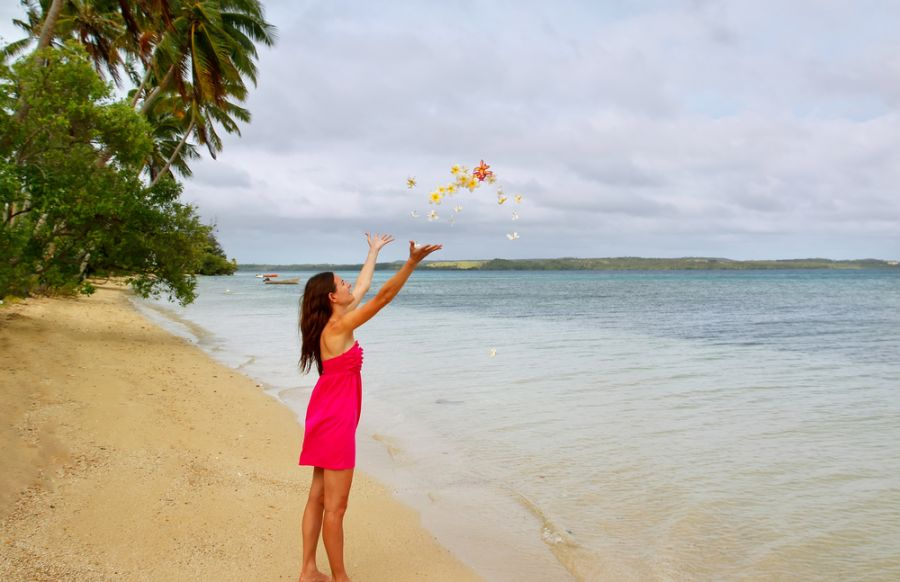 Vava'u Islands A35JP/P Tourist attractions Young woman on a beach throwing flowers in the air